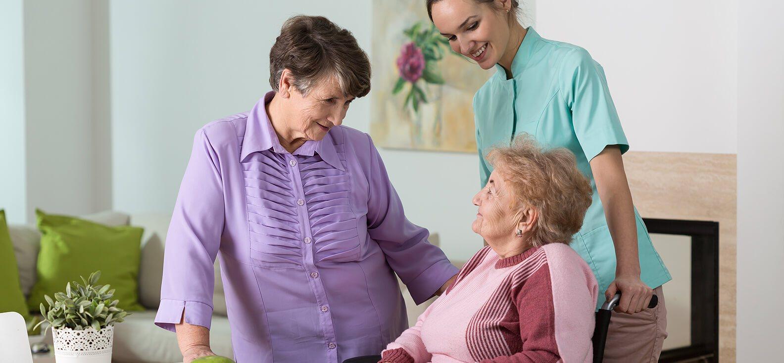 Ein Pflegerin und zwei ältere Damen unterhalten sich