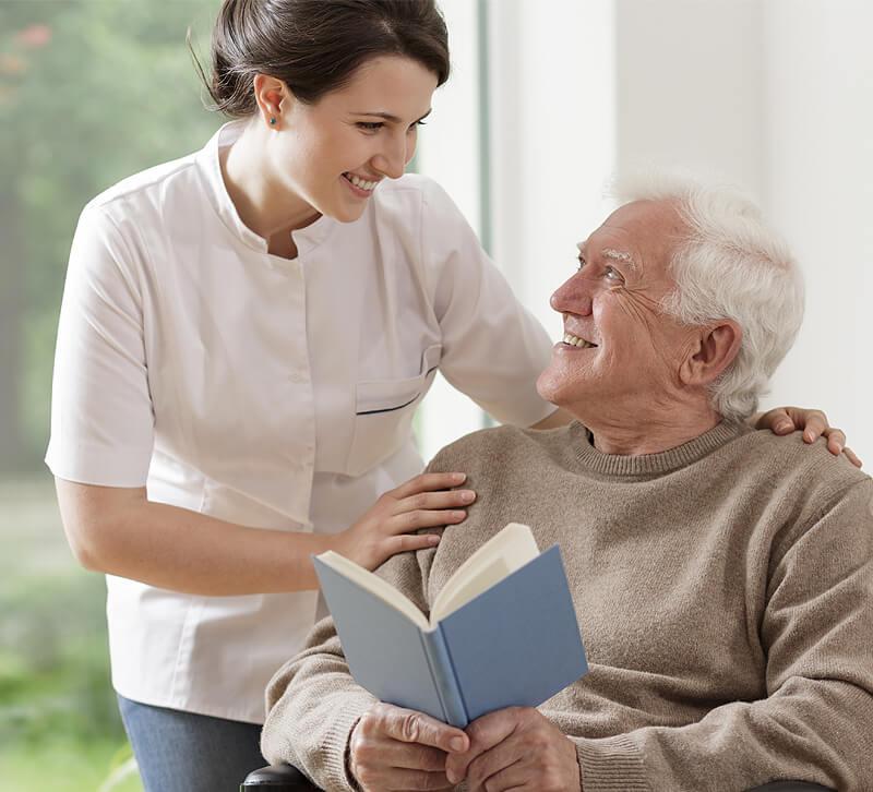 Ein Pflegerin und ein älterer Herr